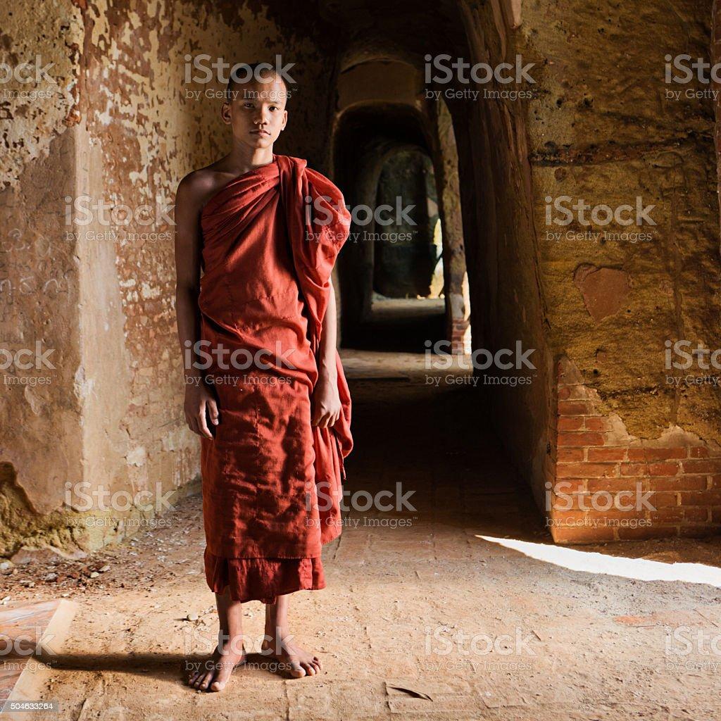 Novice Buddhist monk standing inside the temple stock photo