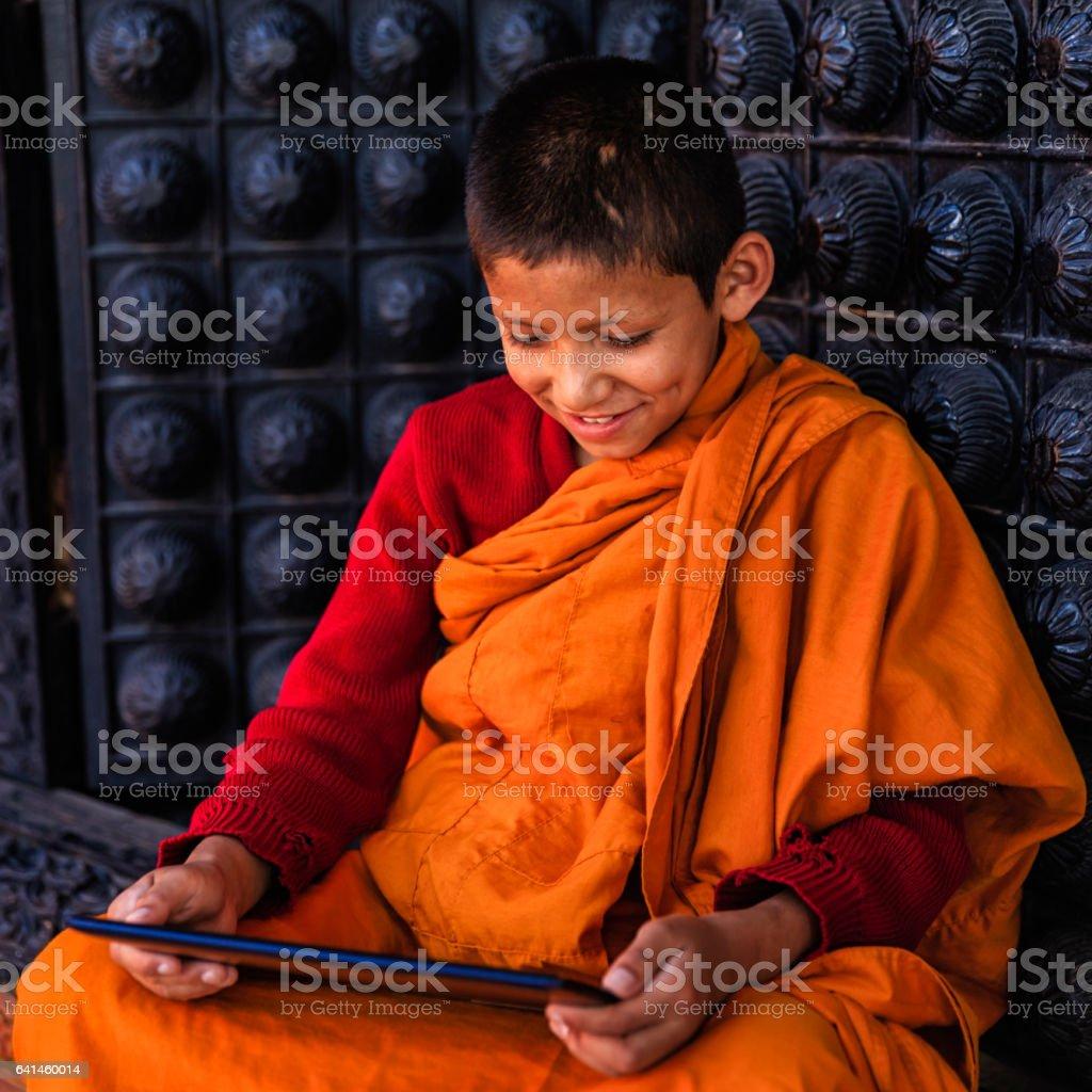 Novice Buddhist monk using digital tablet, Bhaktapur stock photo