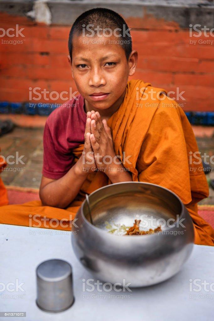 Novice Buddhist monks eating together in monastery, Bhaktapur stock photo