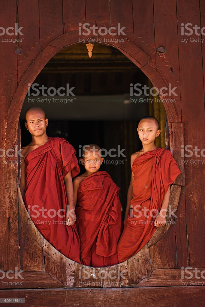 Novice Buddhist monks looking out of the window stock photo