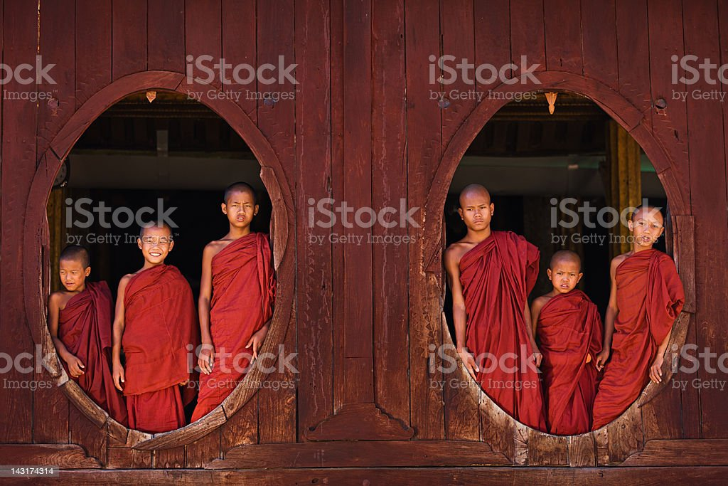 Novice Buddhist monks looking out of the windows royalty-free stock photo