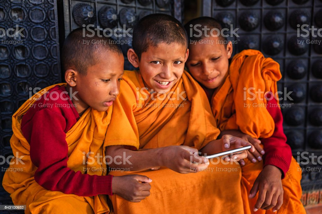 Novice Buddhist monks playing on mobile phone, Bhaktapur stock photo