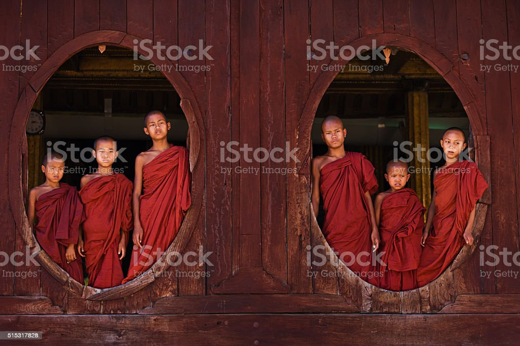 Novice Buddhist monks posing in the window of monastery stock photo