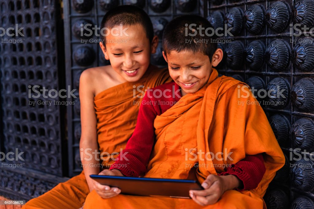 Novice Buddhist monks using digital tablet, Bhaktapur stock photo