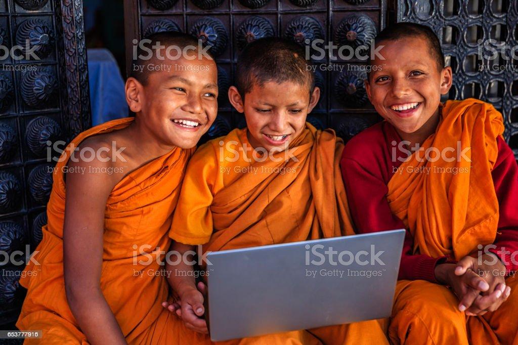 Novice Buddhist monks using laptop, Bhaktapur stock photo