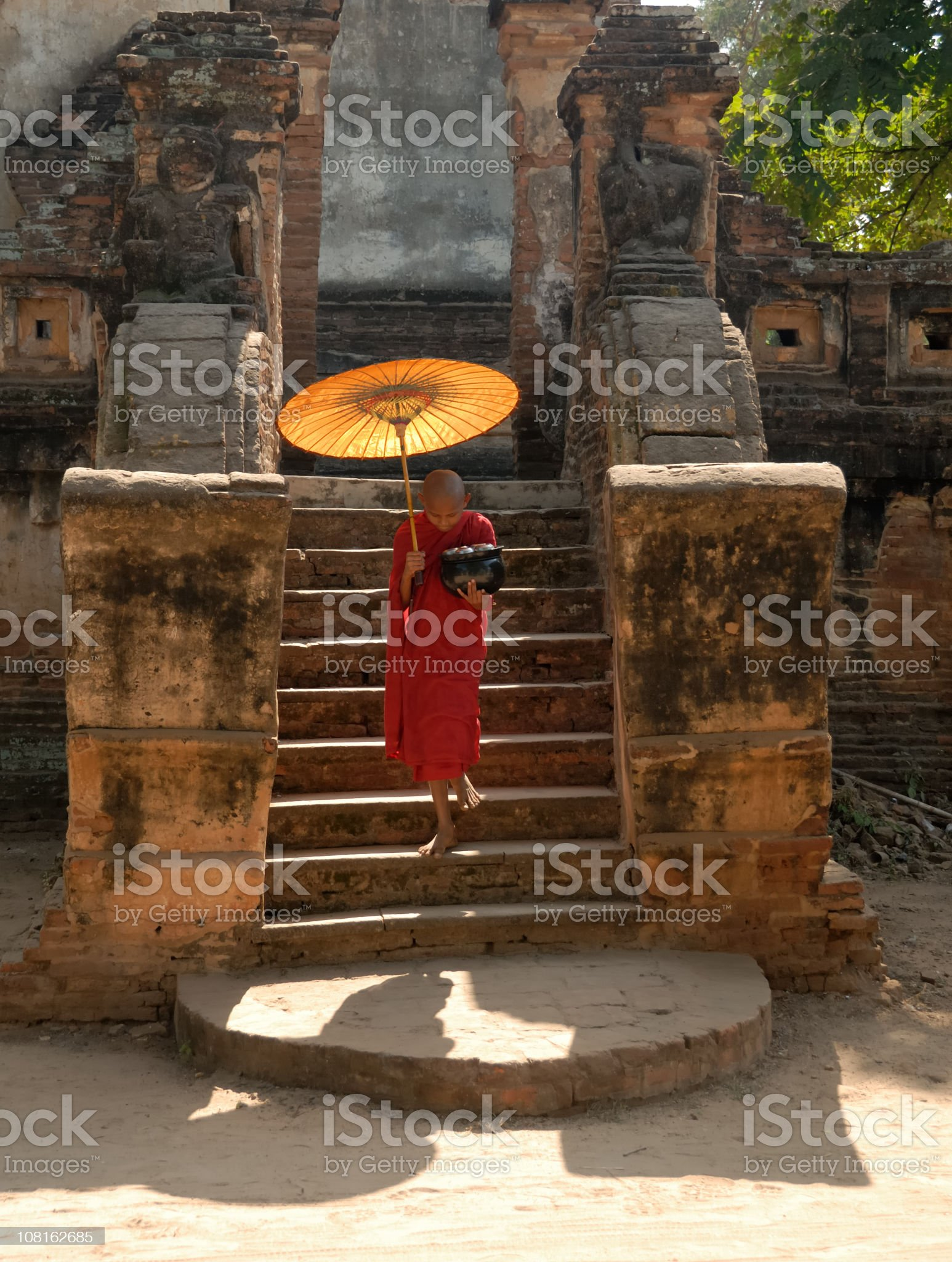 Novice monk with parasol walking down the stairs royalty-free stock photo