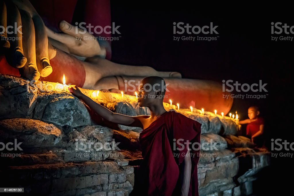 Novice Monks lighting Candles to worship Buddha Temple Bagan Myanmar stock photo