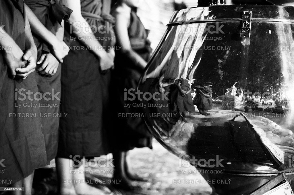 Novice monks next to silver urn stock photo