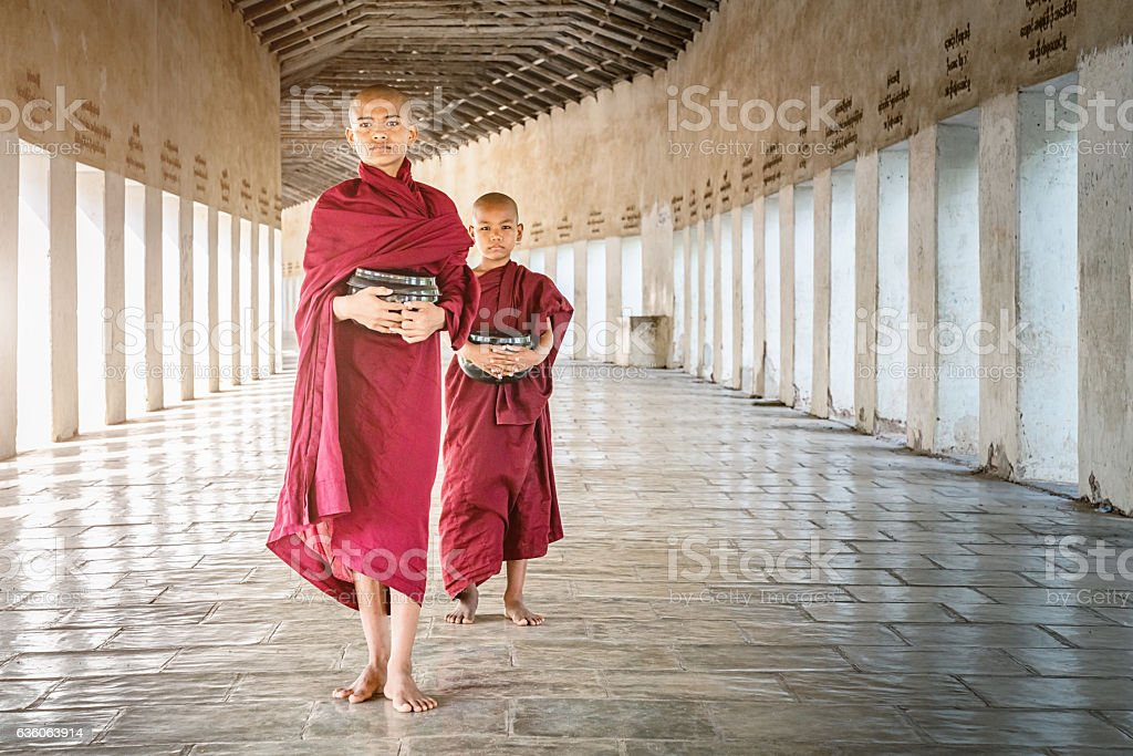 Novice Monks Walking with Alms Bowls Monastery Archway Myanmar stock photo