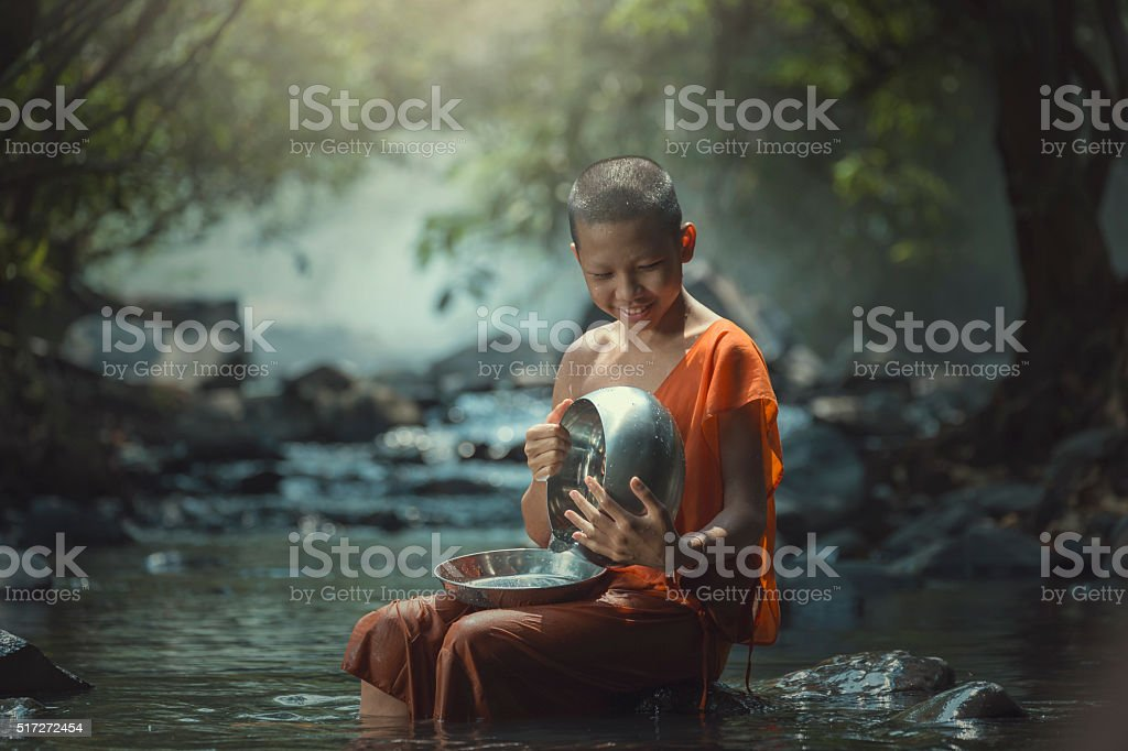 Novice with monk's alms bowl stock photo