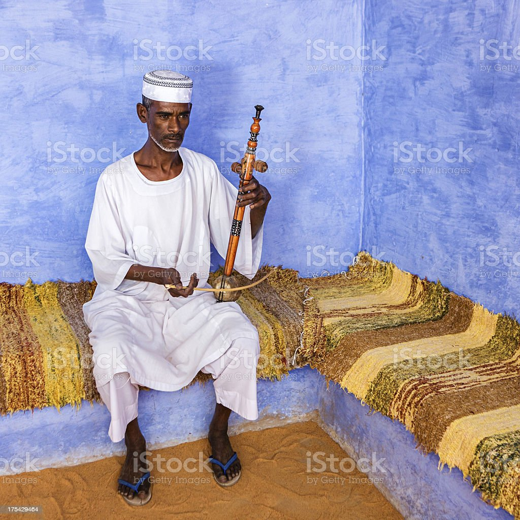 Nubian man playing a rebab in Southern Egypt royalty-free stock photo