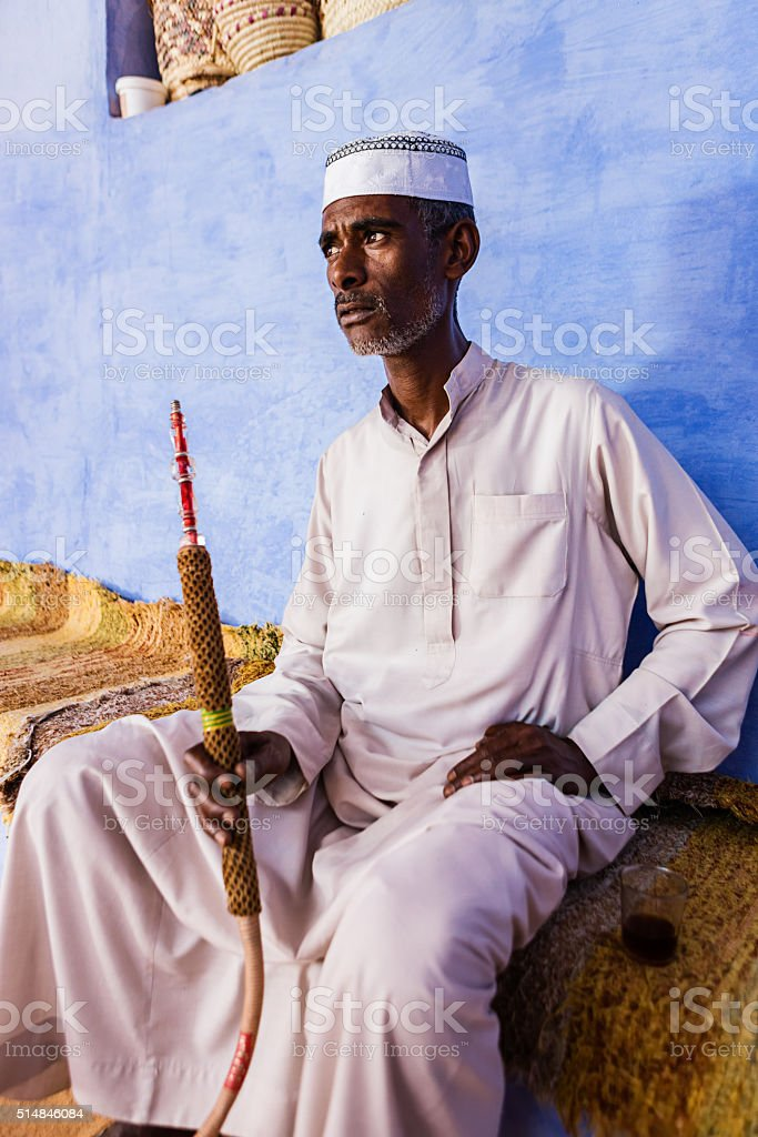Nubian man smoking  sheesha - waterpipe in Southern Egypt stock photo