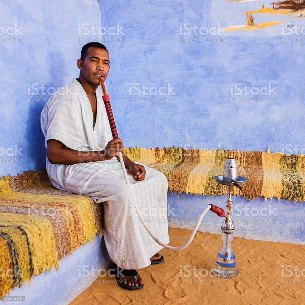 Nubian man smoking waterpipe in Southern Egypt stock photo