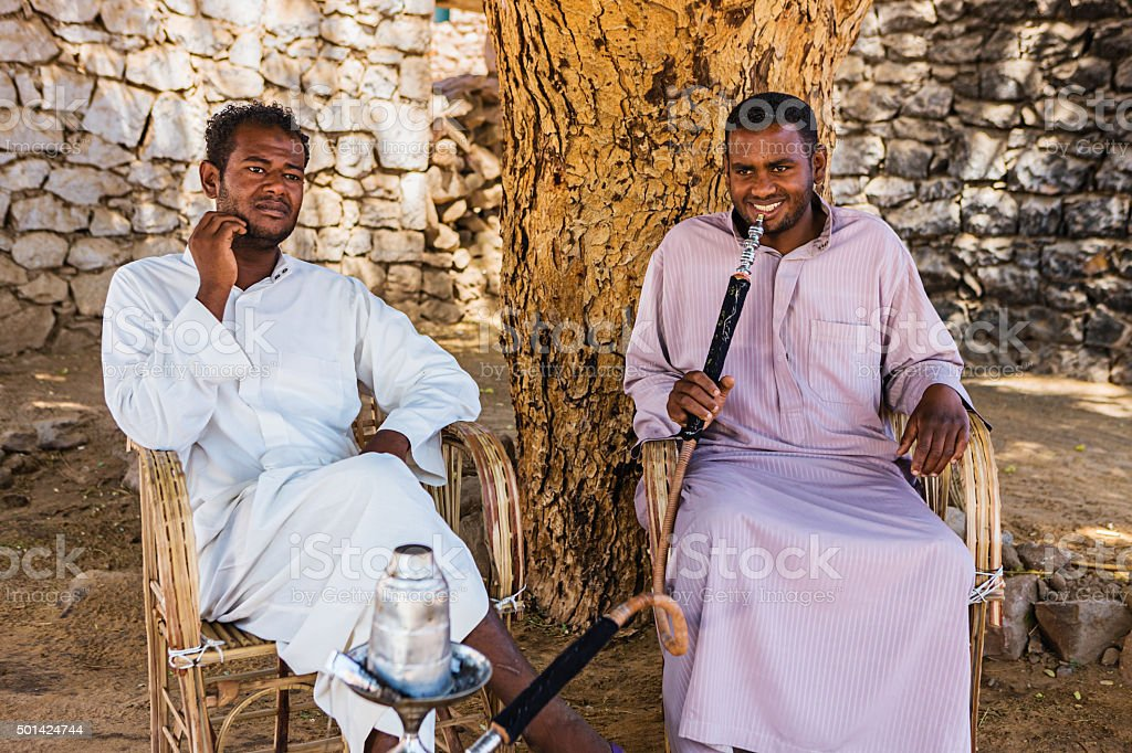 Nubian men smoking waterpipe in Southern Egypt stock photo