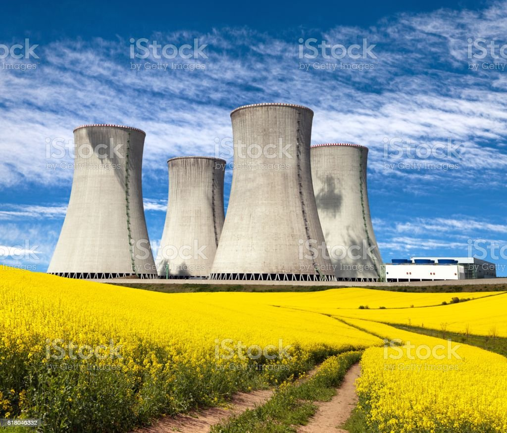 Nuclear power plant and field of rapeseed stock photo