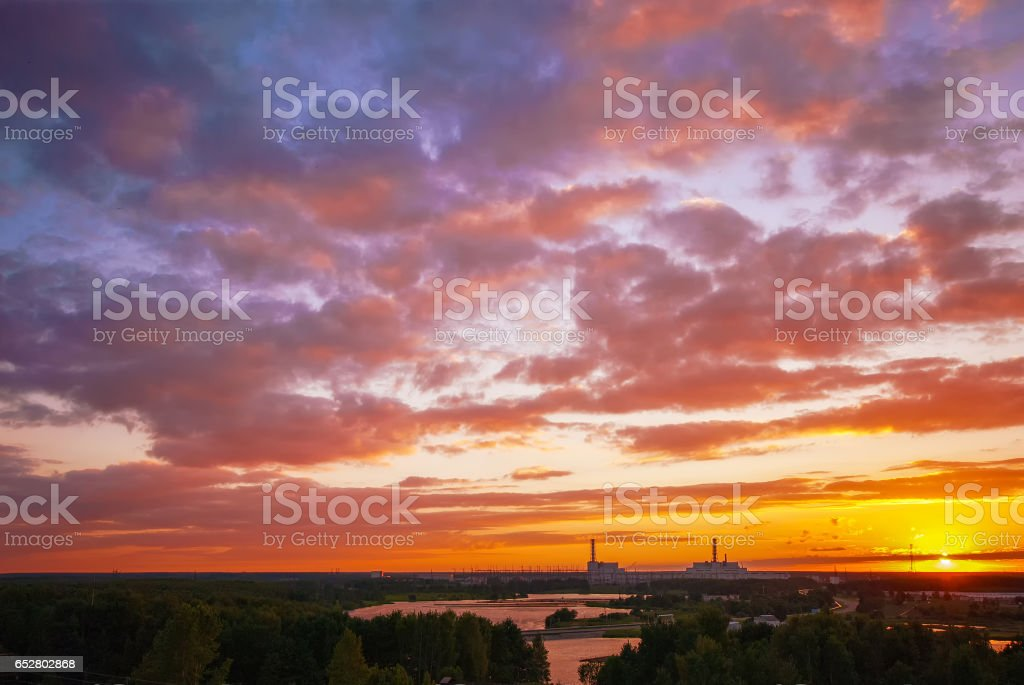 Nuclear power plant at beautiful sunset with intense blue and pink cloudy sky in summer evening stock photo