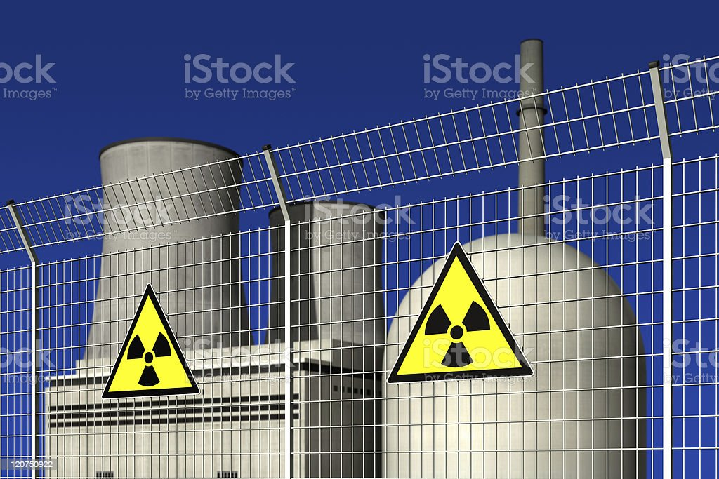 Nuclear power plant behind a barrier fence with warning signs royalty-free stock photo
