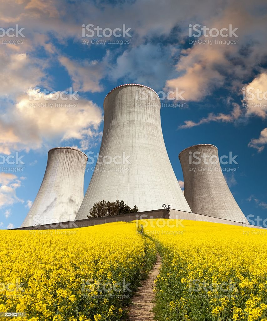 Nuclear power plant Dukovany with golden flowering field of rapeseed stock photo