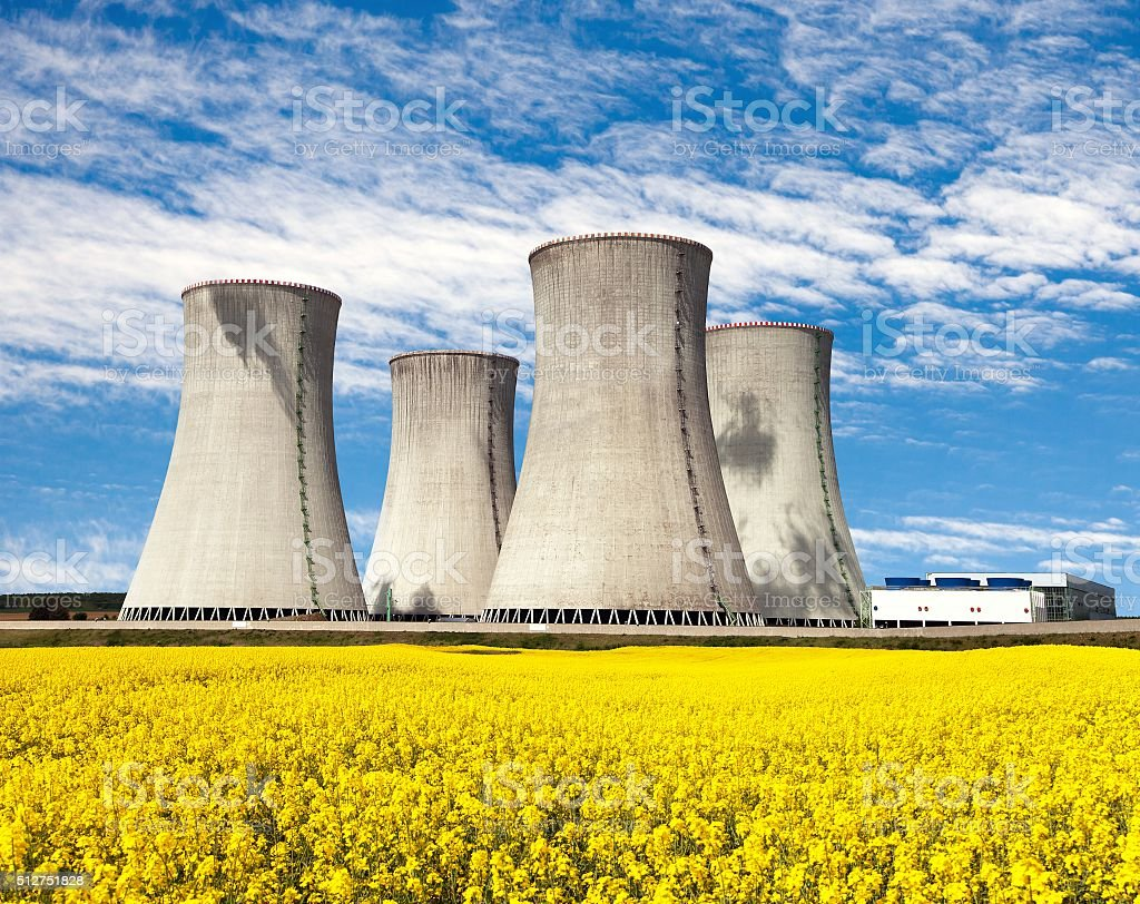 Nuclear power plant Dukovany with golden glowering field of rapeseed stock photo