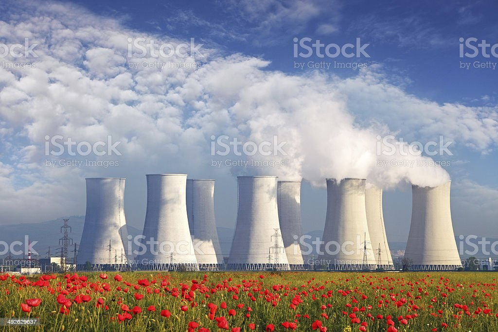 Nuclear Power plant with red field and blue sky stock photo