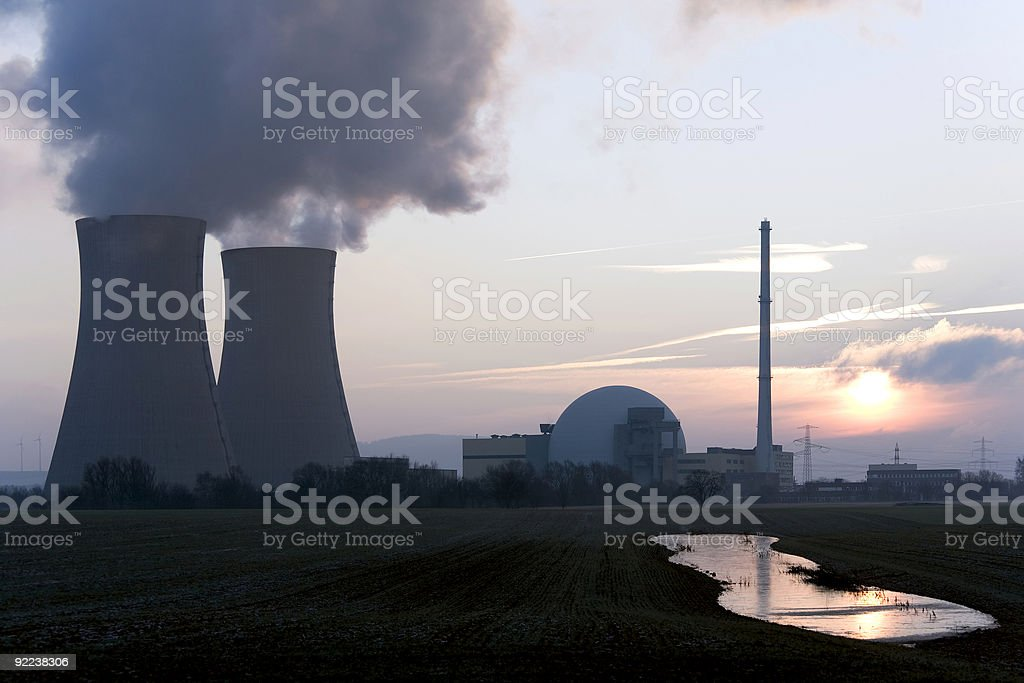 Nuclear power station at sunrise with steaming cooling towers royalty-free stock photo