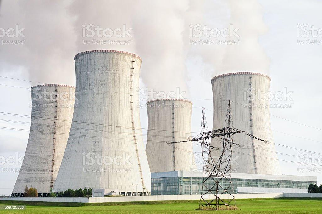 Nuclear power station with four steaming cooling towers. stock photo
