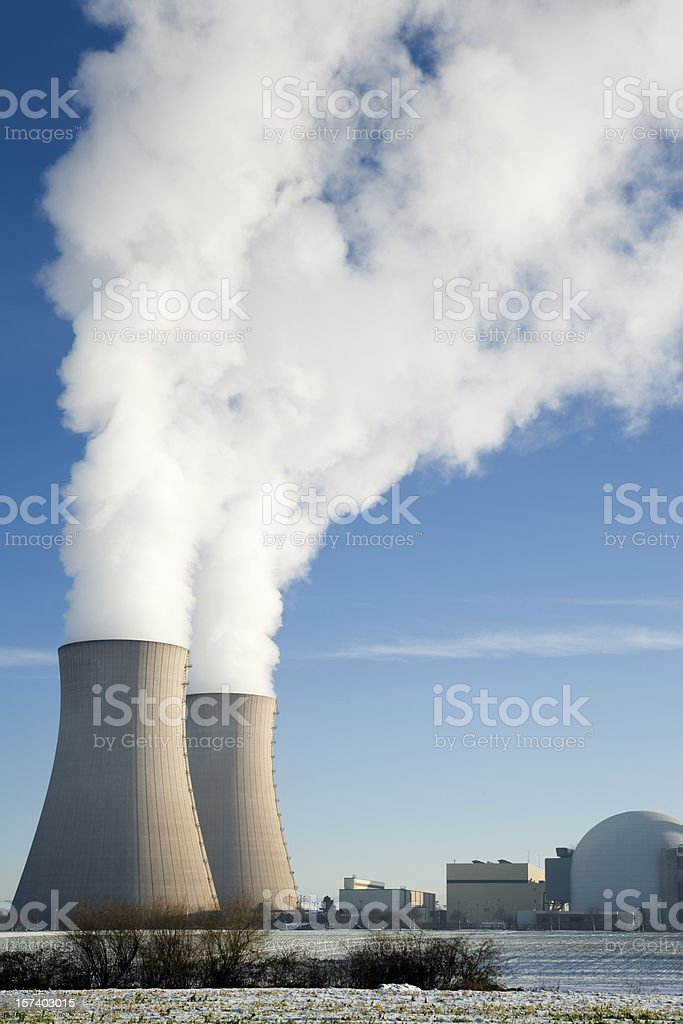Nuclear power station with two steaming cooling towers in winter stock photo