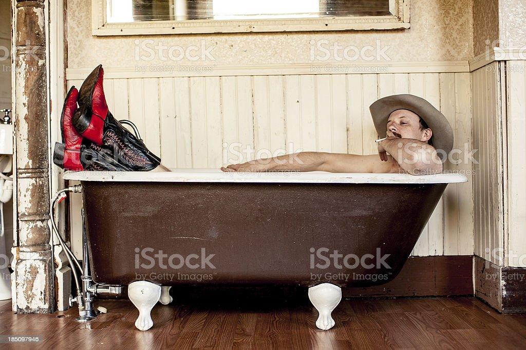 Nude Cowboy in Tub Wearing Hat and Boots royalty-free stock photo