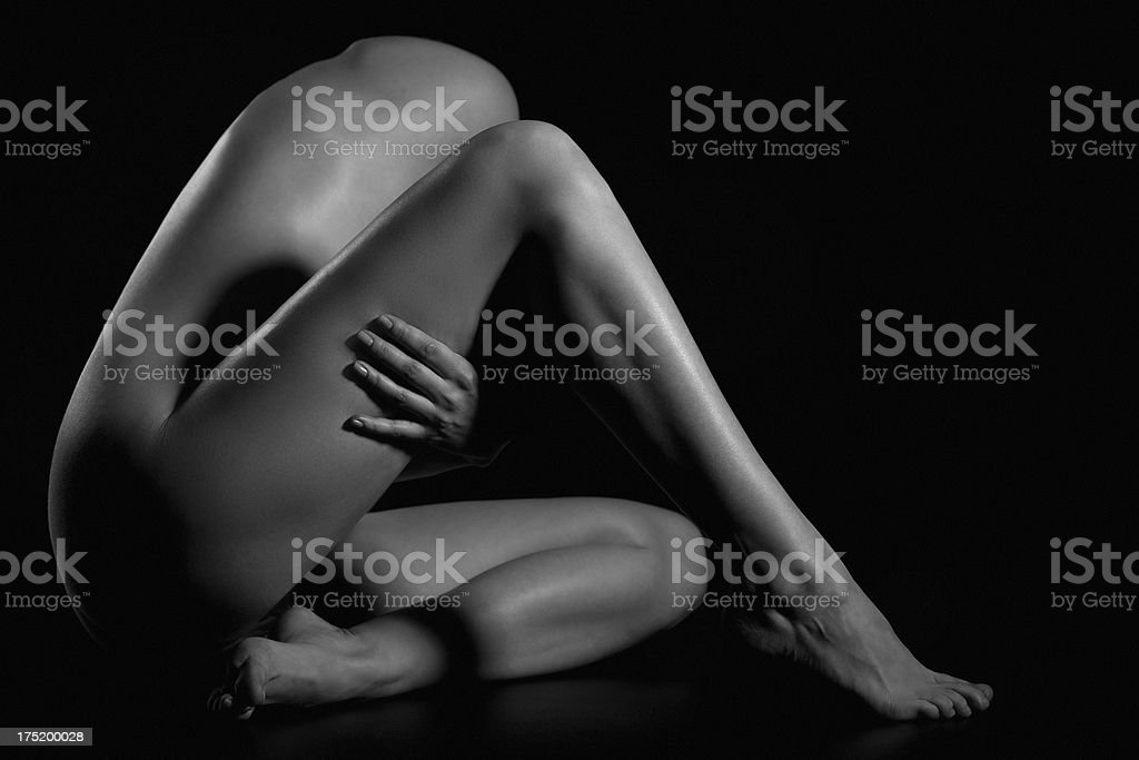 Nude female body on black background stock photo