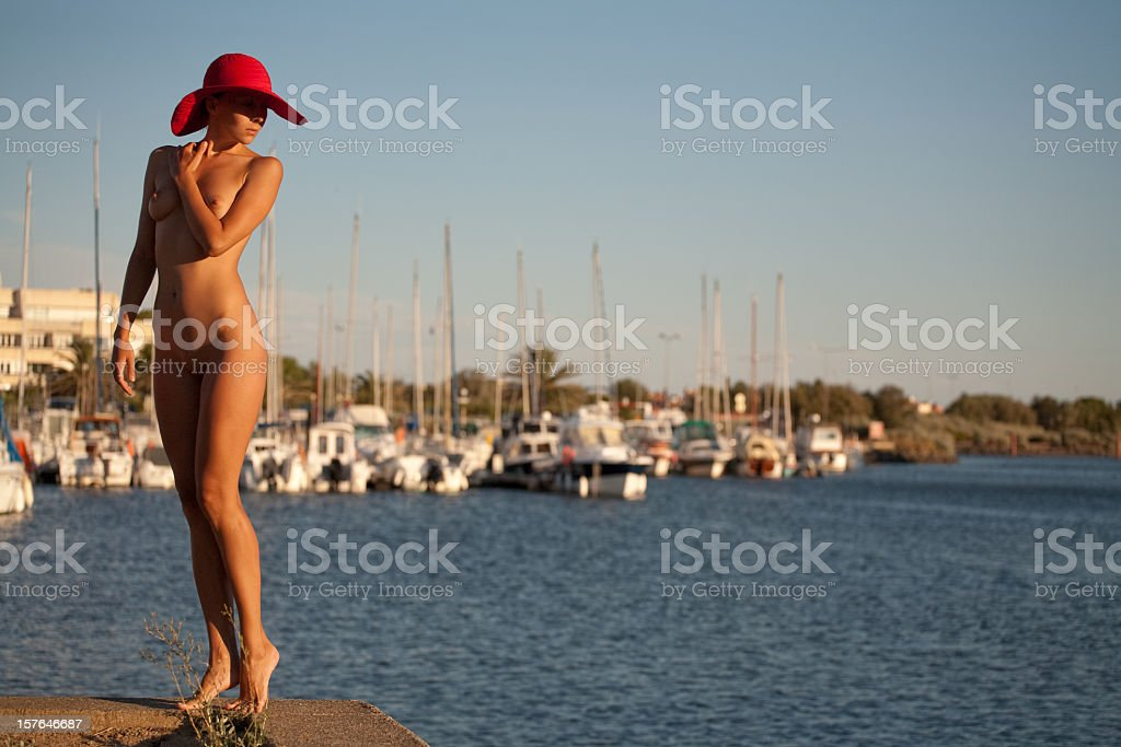 nude girl in red hat on pier stock photo