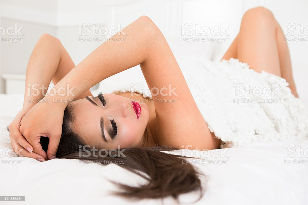 Nude woman hugging blanket laying on bed royalty-free stock photo