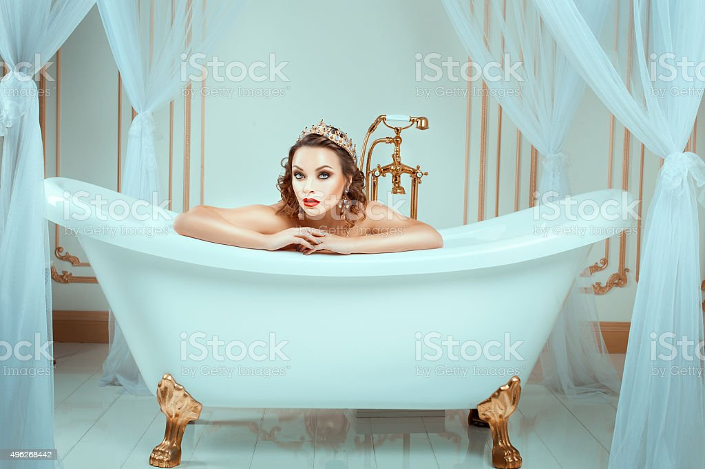 Nude woman sitting in expensive jewelry bath. stock photo