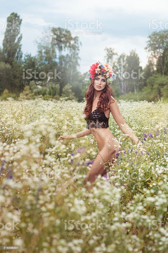 Nude woman standing in a field of flowers. stock photo