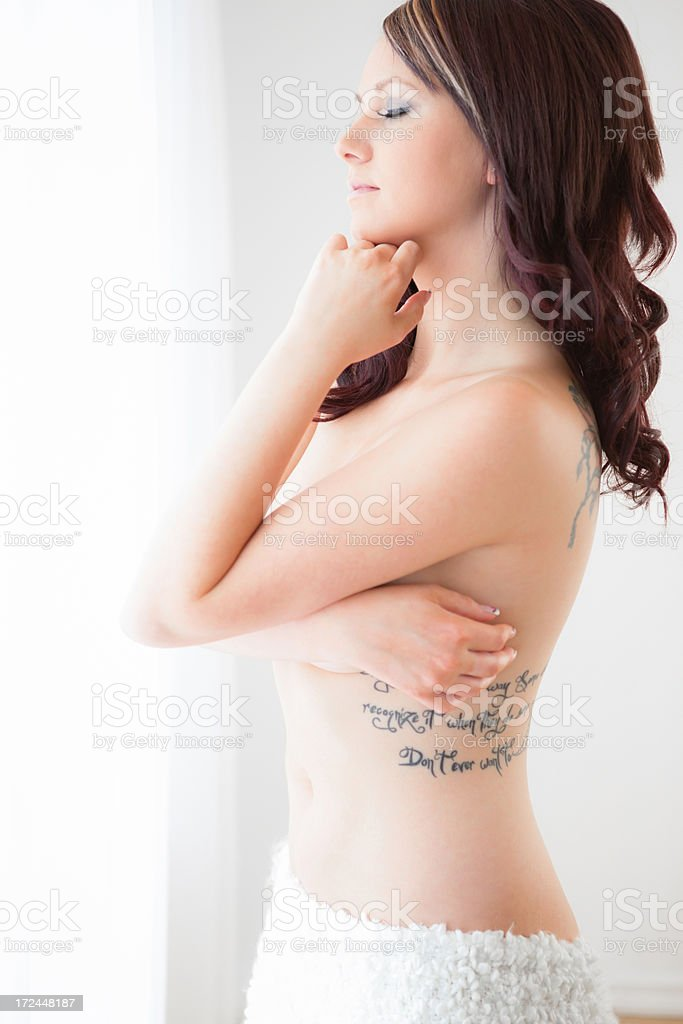 Nude woman standing in front of window royalty-free stock photo