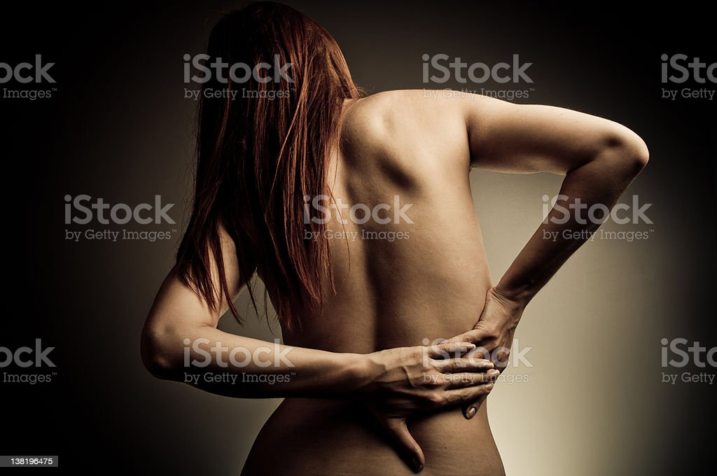 Nude woman touching her back as if in pain royalty-free stock photo