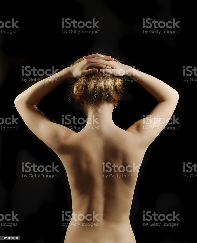 Nude young woman from back with arms raised royalty-free stock photo