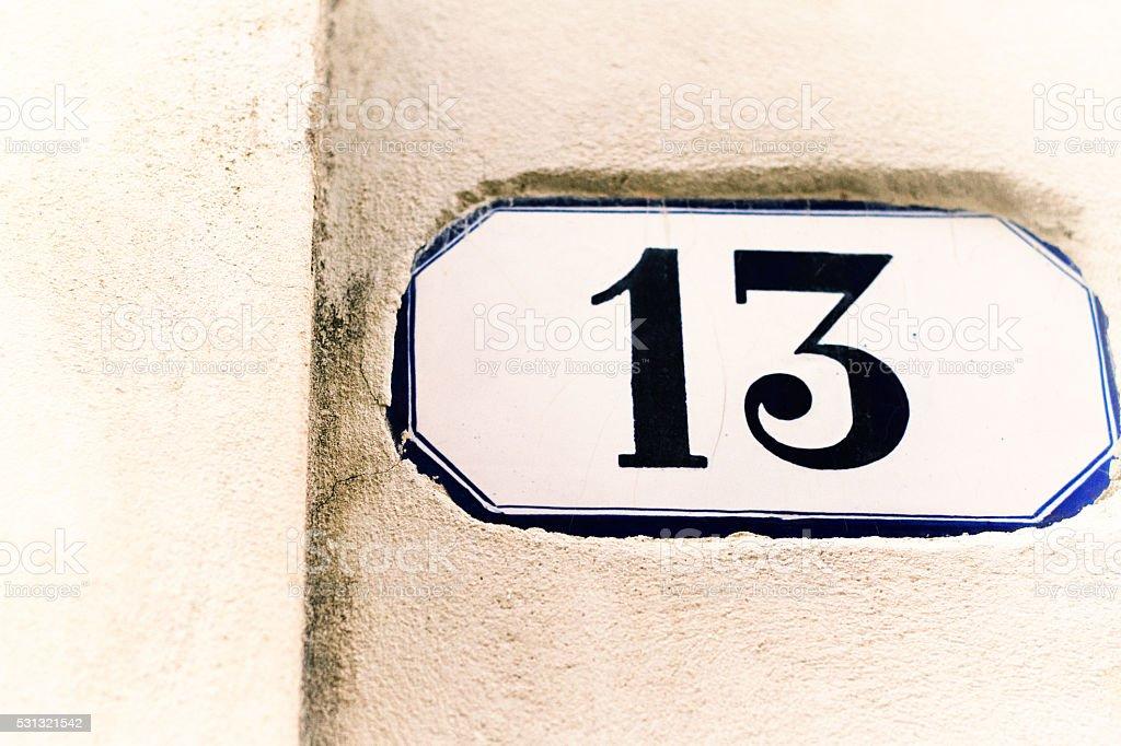 Number 13 Vintage Ceramic Address Tile On White Wall stock photo