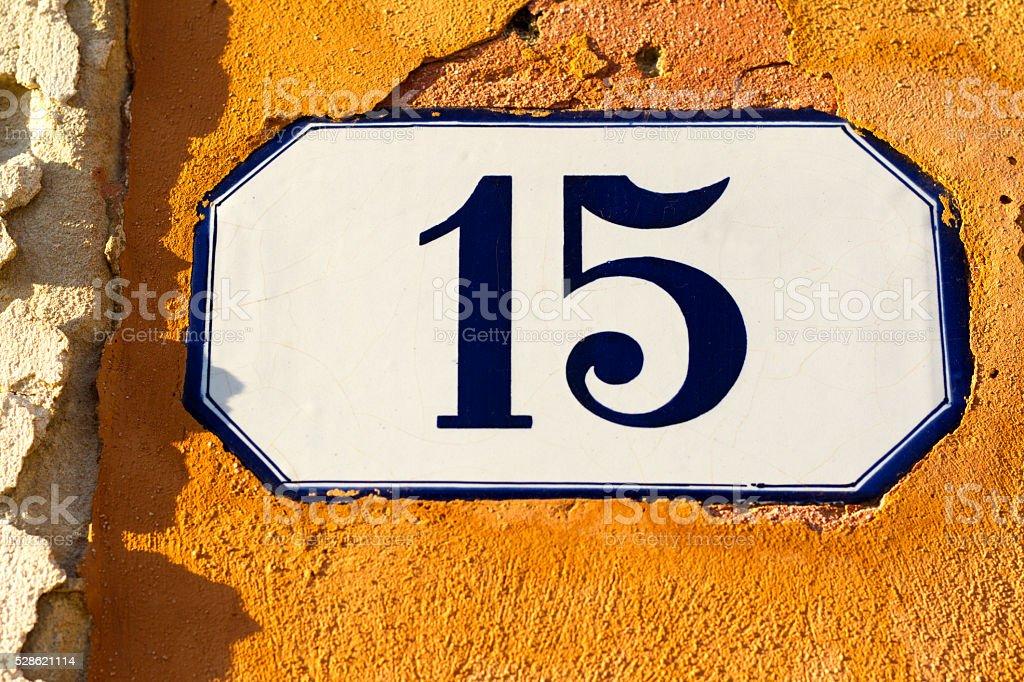 Number 15 Ceramic Address Plaque in Vibrant Old Orange Wall stock photo