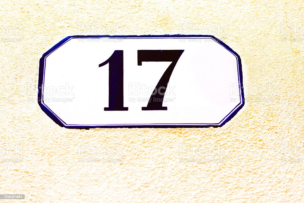 Number 17 Street Address Tile On Yellow Stucco Wall (Close-Up) stock photo