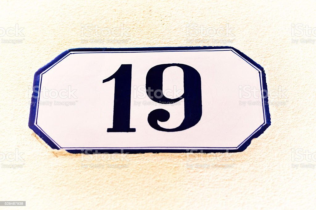 Number 19 Street Address Tile On Yellow Stucco Wall (Close-Up) stock photo