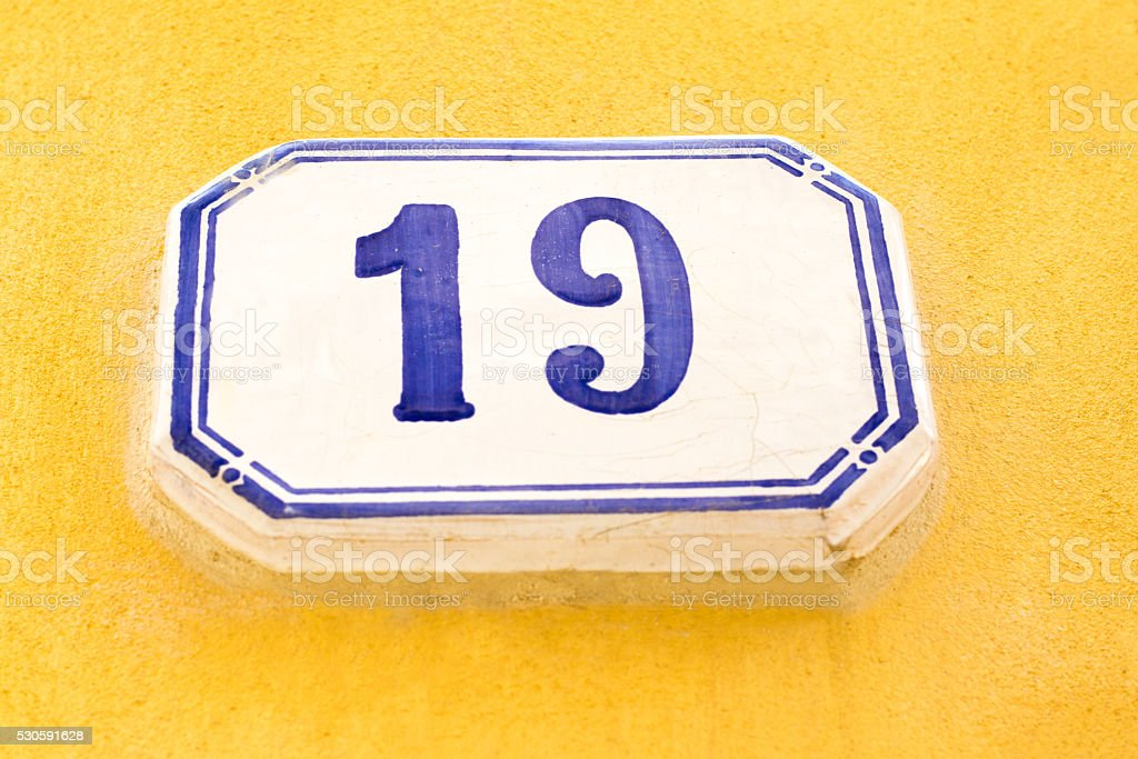 Number 19 Vintage Street Address Tile On Yellow Wall (Close-Up) stock photo