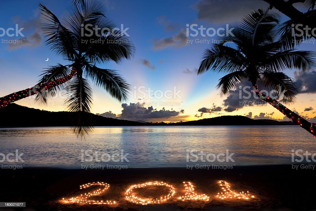 number 2011 in sand with Christmas lights at a beach stock photo