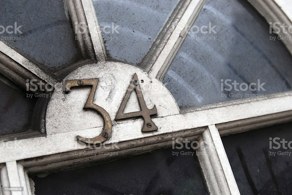 Number 34 on dirty door stock photo