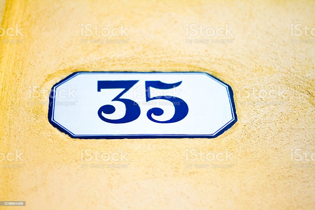 Number 35 Blue and White Address Tile, Yellow Wall (Close-Up) stock photo