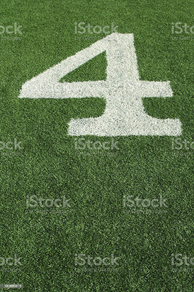Number 4 (four) painted in white on green football astroturf royalty-free stock photo