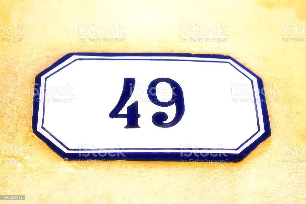 Number 49 Vintage Ceramic Street Address Tile, Yellow Wall stock photo