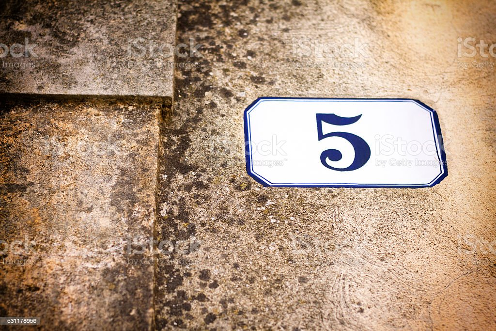 Number 5 Ceramic Street Address Tile on Old Tan Wall stock photo