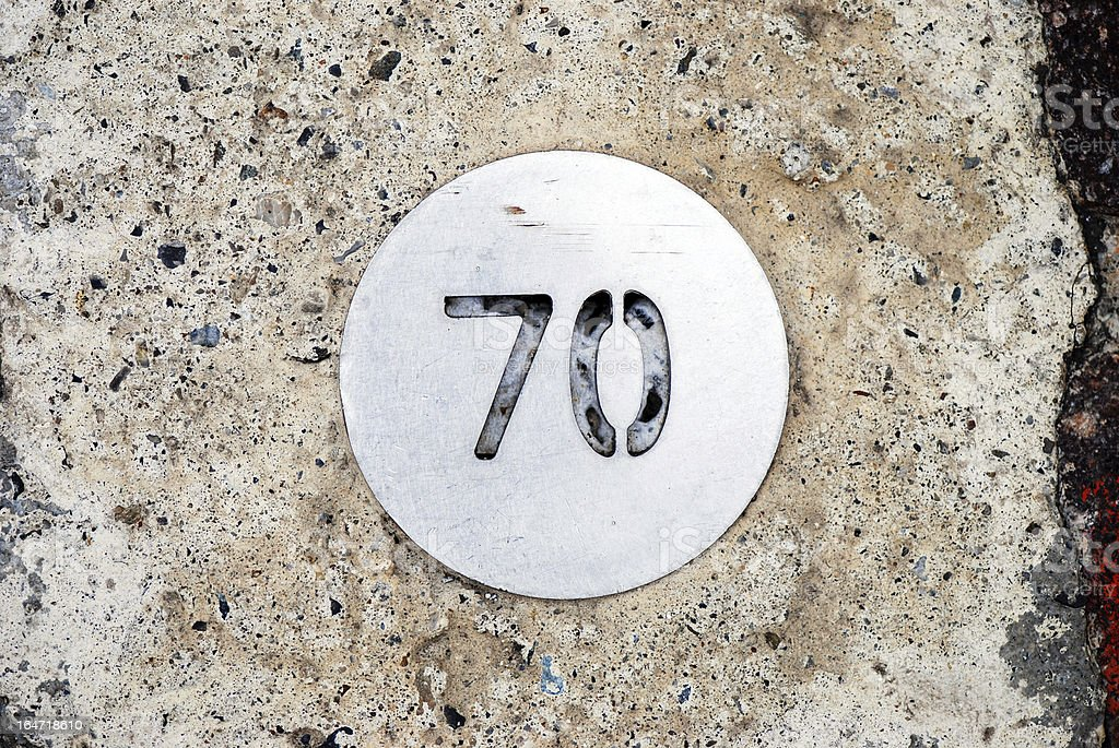 Number 70 on circular metal plate stock photo