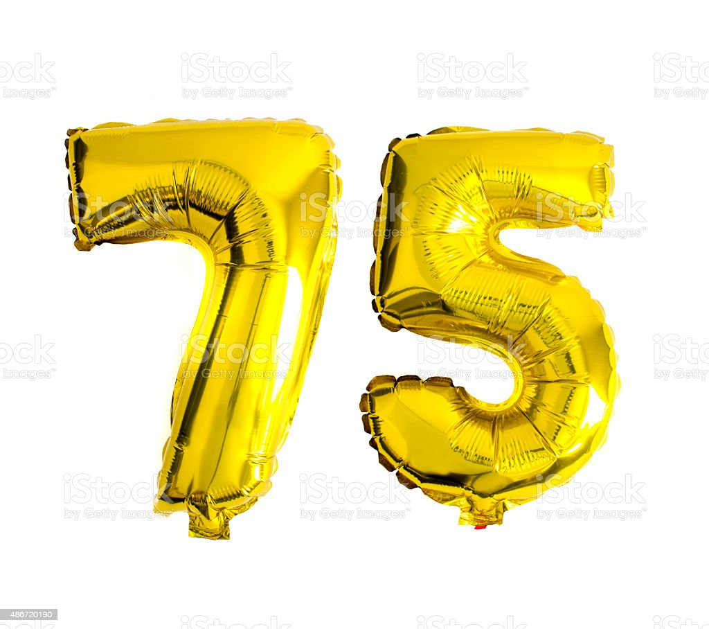 Number 75 written with golden foil helium balloons stock photo