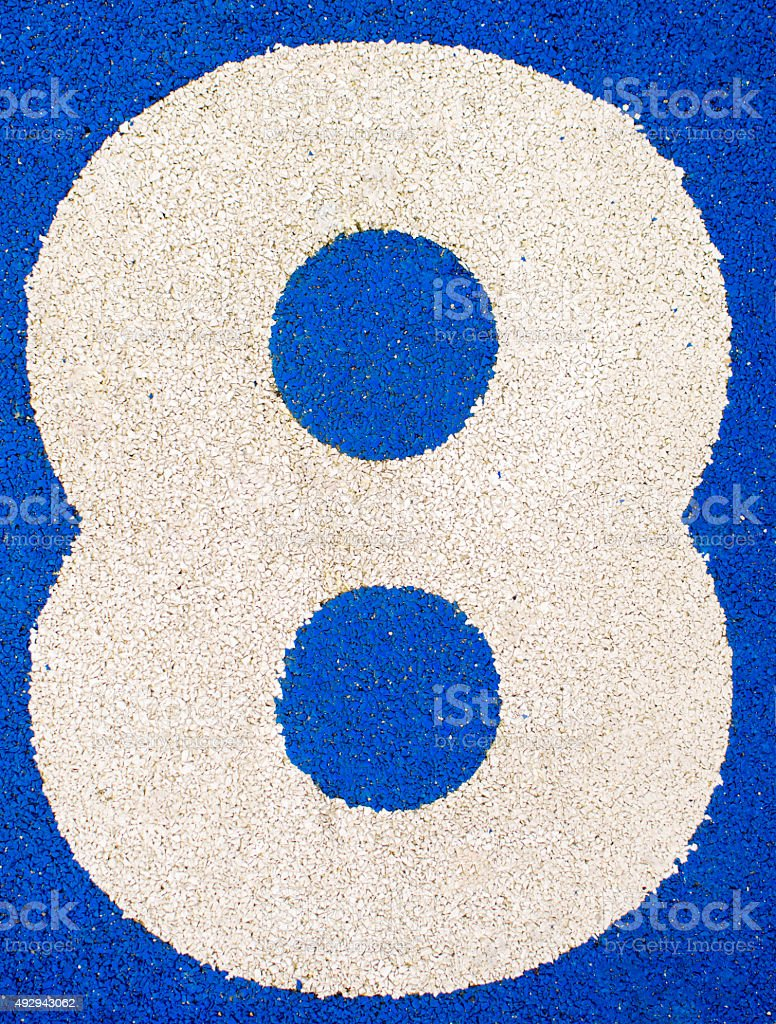 Number eight on a running track. Number on blue background stock photo